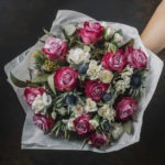 Flower bouquet with pink roses, blue thistle, mimosa and white r